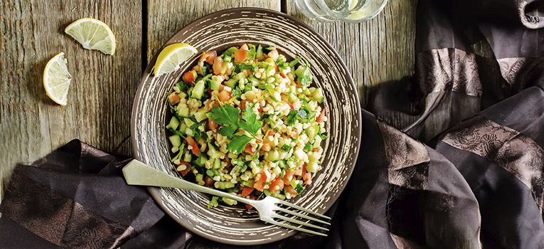 salad with bulgur and vegetables, Tabbouleh, on a dark wood background. tinting. selective focus on the parsley